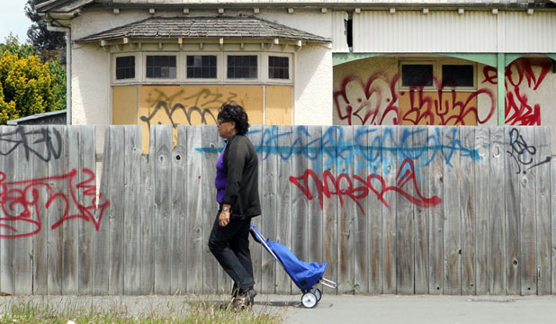 DISHEARTENING: A member of the public passes a graffiti-defaced property in Linwood. It is not known who did this tagging.