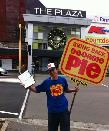 PIE MAN: Whakatane man Grant Duffield, 29, stands outside The Plaza with his Georgie Pie sign and petition in tow.