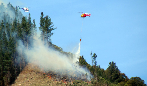 AIRDROP: A helicopter pours a monsoon bucket over a fire in scrubland at Upper Takaka.