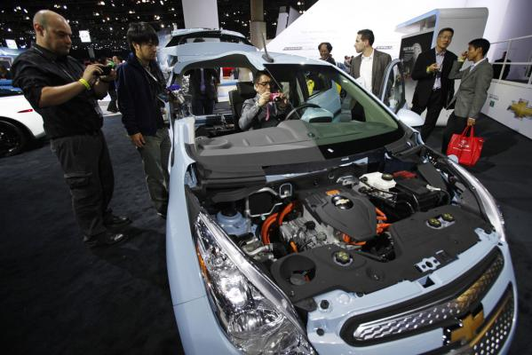 Members of the media look at a sectioned 2013 Chevrolet Spark - known as the Holden Barina Spark in New Zealand - Electric Vehicle at the 2012 Los Angeles Auto Show in Los Angeles.