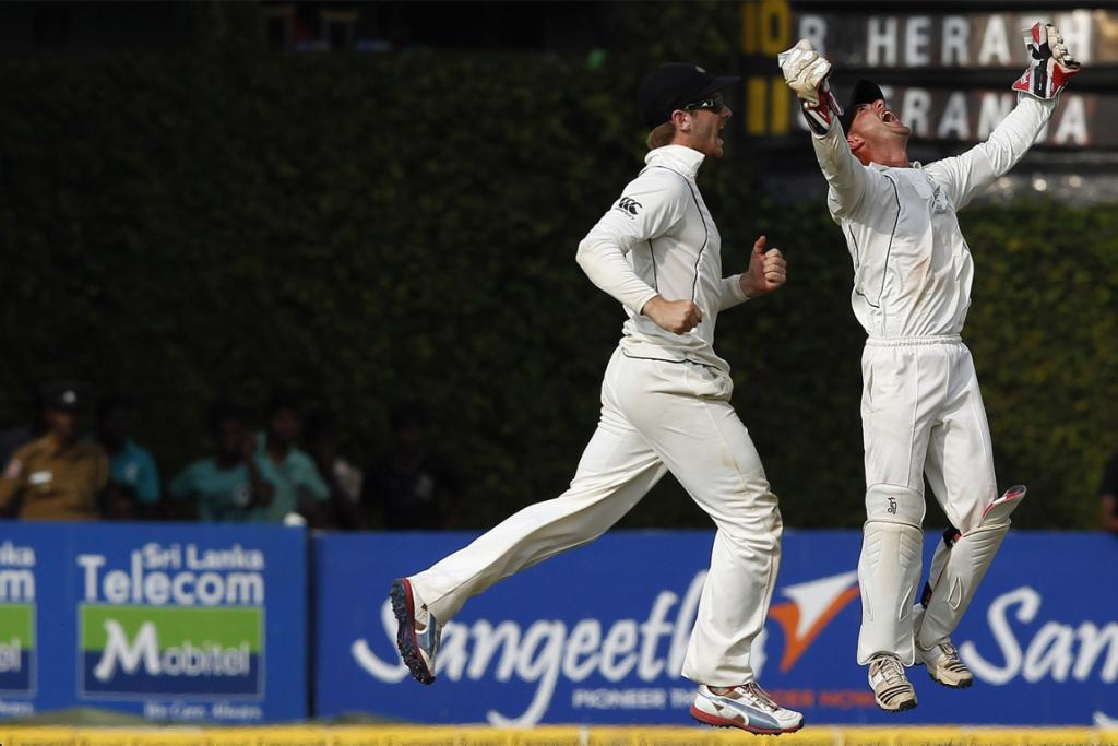 Kane Williamson (left) and Kruger van Wyk celebrate as New Zealand claim the final wicket to seal victory.