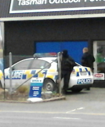 MEN IN BLACK: Armed Offenders Squad officers at the scene of the arrest in Gladstone Rd, Richmond.