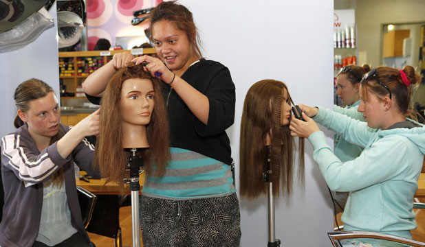 BRUSHING UP: Salisbury School pupils, from left, Leana Shaw, 17, Grace Powell, 15, and Connie Leslie, 15, try out  hair styles on models during a visit to Nelson Marlborough Institute of Technology.