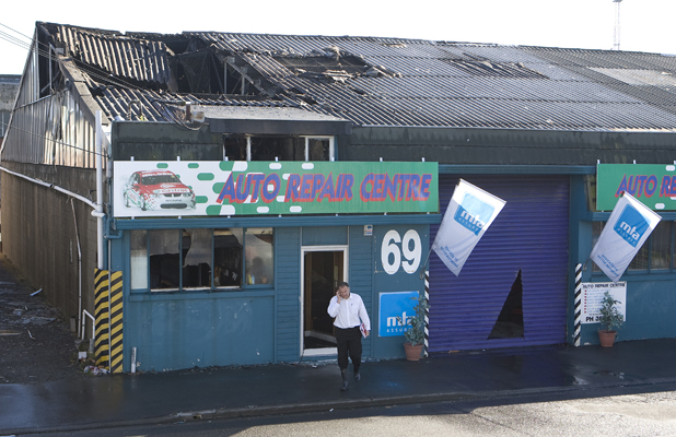 INVESTIGATION: A police officer leaves the Auto Repair Centre in Byron St, Sydenham, after it caught fire in September 2008.