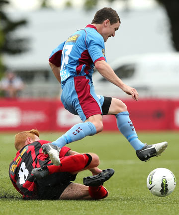 FLEET-FOOTED: Hawke's Bay United's Fergus Neil leaps as he is tackled by Canterbury United's Aaron Clapham at English Park in Christchurch.