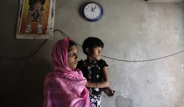 SURVIVOR: Ruma Akhter, 23, who survived a devastating fire in a garment factory, stands inside her slum room with her daughter Nishi, 6.