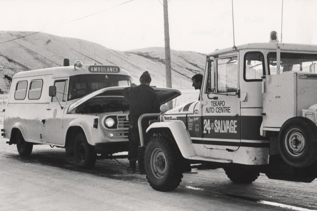 """EMERGENCY BREAKDOWN: Several people correctly said that this photo shows Andy Green of Tekapo Auto Centre lending a helping hand to an ambulance. Andy was involved with the ambulance service at Tekapo for many years. Do you know more?  UPDATE [01/12/2012]: Chris Green provided some additional information on this 1980s photo of Andy Green, then owner of Tekapo Auto Centre. """"The Twizel Ministry of Works ambulance had broken down at Forks Bridge in icy conditions,"""" Chris wrote. """"Andy towed it to the top of the rise at the end of Braemar Rd and checked out the problem."""""""
