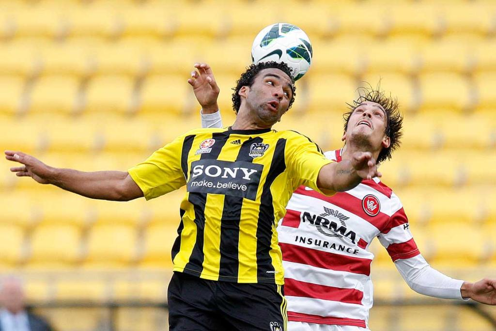 Paul Ifill of the Phoenix and Jerome Polenz of the Wanderers go for the ball.