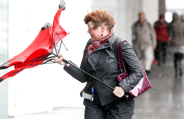 ANOTHER ONE BITES THE DUST: A woman looks at her umbrella, destroyed by Wellington winds.