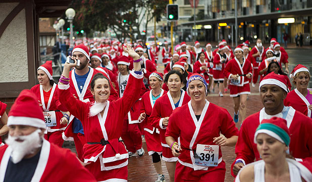 LAUGHING ALL THE WAY: More than 1200 people donned the red suit for the Great KidsCan Santa Run in Auckland.