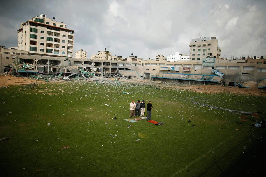 DECEMBER 6: Palestinian security guards pray at a soccer stadium, which witnesses said was destroyed in an Israeli air strike during the recent eight day conflict in Gaza City. Eight days of Israeli air strikes on Gaza and cross-border Palestinian rocket attacks ended in an Egyptian-brokered truce agreement last month, calling on Israel to ease restrictions on the territory.