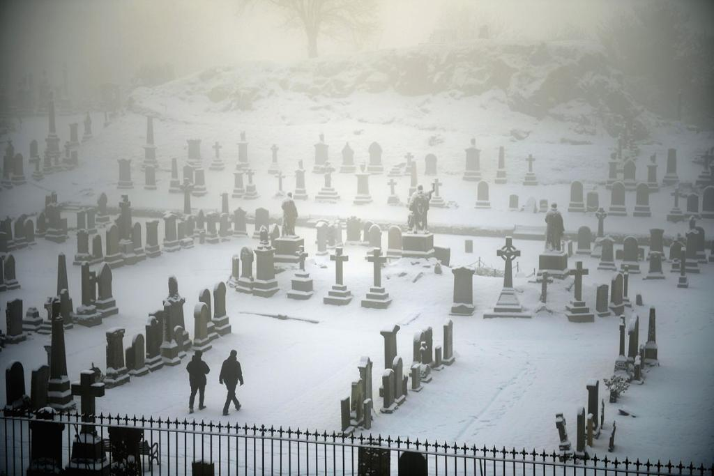 DECEMBER 4: Two men walk through Stirling Castle graveyard in Stirling, Scotland. Snow and sleet has hit many parts of Scotland with heavier falls expected over higher grounds.