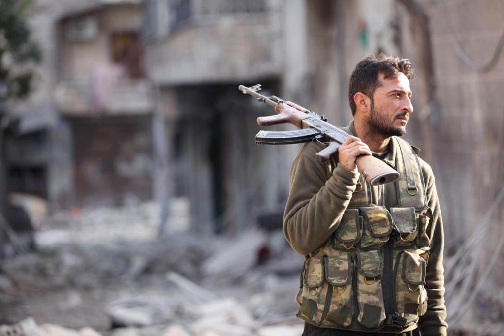 DECEMBER 3: A Free Syrian Army fighter holds his rifle as he stands on a damaged street in Aleppo's Karm al-Jabal district.