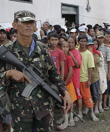 LINE FOR HELP: A soldier stands guard as typhoon evacuees queue for relief goods outside a local government town centre in New Bataan.