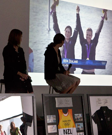 GOLDEN GLORY: Olympic gold medallists Polly Powrie, left, and Jo Aleh watch themselves on the big screen in Christchurch yesterday.