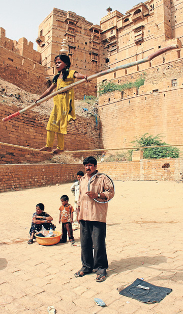HIGH AIMS: A young slack-wire walker learns the skill in the shadow of the ancient Golden Fort, located in the Thar Desert in Rajasthan, India.