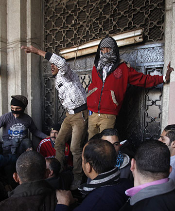 PROTEST BUILDS: Protesters block the gate of a government building near Tahrir Square in Cairo.