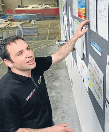 CONVINCED: Fibreglass Innovations owner Gareth Dykes with the 5S workplace management plan his business is using under lean manufacturing to improve efficiency.
