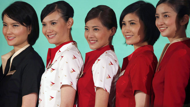 IN HAPPIER TIMES: Flight attendants and ground crew of Cathay Pacific Airways present their new uniforms in Hong Kong last June.