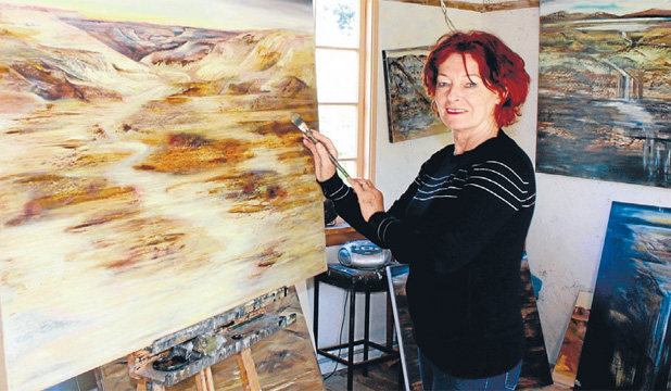 BANNOCKBURN VIEWS: Central Otago artist Gail de Jong in her studio working on pieces that feature in her latest exhibit that is on display in Gore.