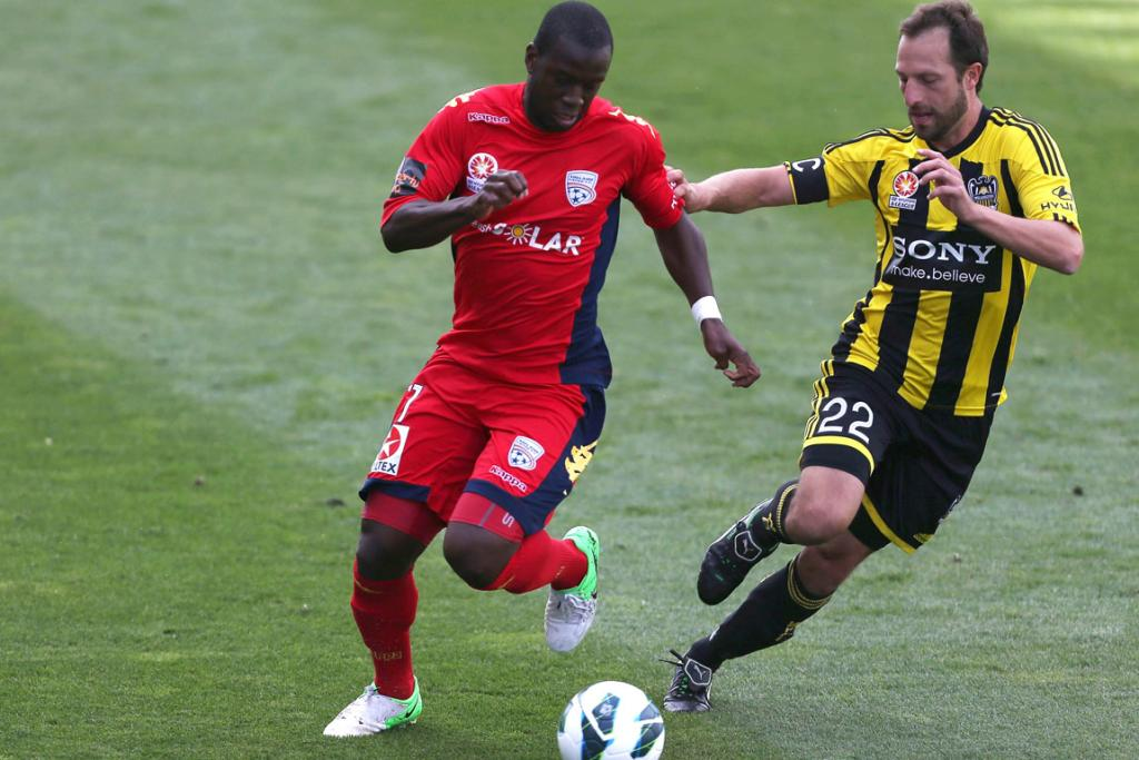Bruce Djite of Adelaide is challenged by Andrew Durante of Phoenix during the round 11 A-League match between Adelaide United and the Wellington Phoenix.
