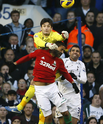 CHALLENGE: Tottenham Hotspur's goalkeeper Hugo Lloris punches the ball as he is challenged by Swansea City's Luke Moore.