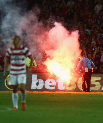 FIRING UP: Officials attempt to remove a flare thrown onto the field during the match between Sydney FC and Western Sydney.