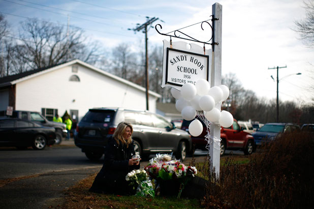 Massacre: A woman places flowers near Sandy Hook Elementary School in Sandy Hook, Connecticut.
