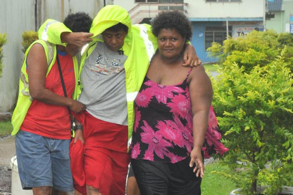 A man is helped to shelter from Cyclone Evan.