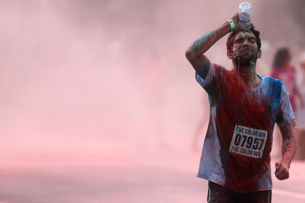 DECEMBER 18: A man runs during the The Color Run in Rio de Janeiro, Brazil. The Color Run is a 5 km race where runners are hit with a powder of a different color at each kilometer they pass.