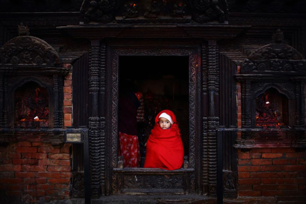 DECEMBER 19: A girl looks out from the entrance door of a temple as her mother offers daily prayers in Lalitpur, Nepal.
