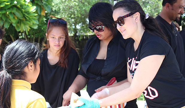 FREE LUNCH: MIT graduates Te-Aorere Salter, Tasi Saatoe and Hollie Ripata serve students of Wymondley Road School.