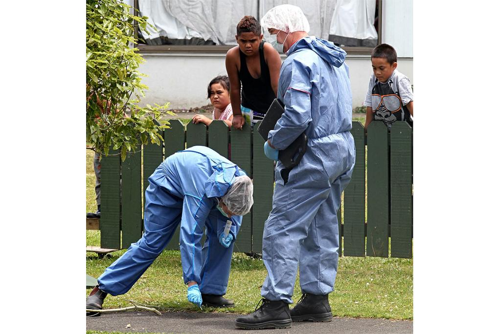 Neighbours watch on as forensic scientists gather evidence at the scene of a homicide in Ranui.