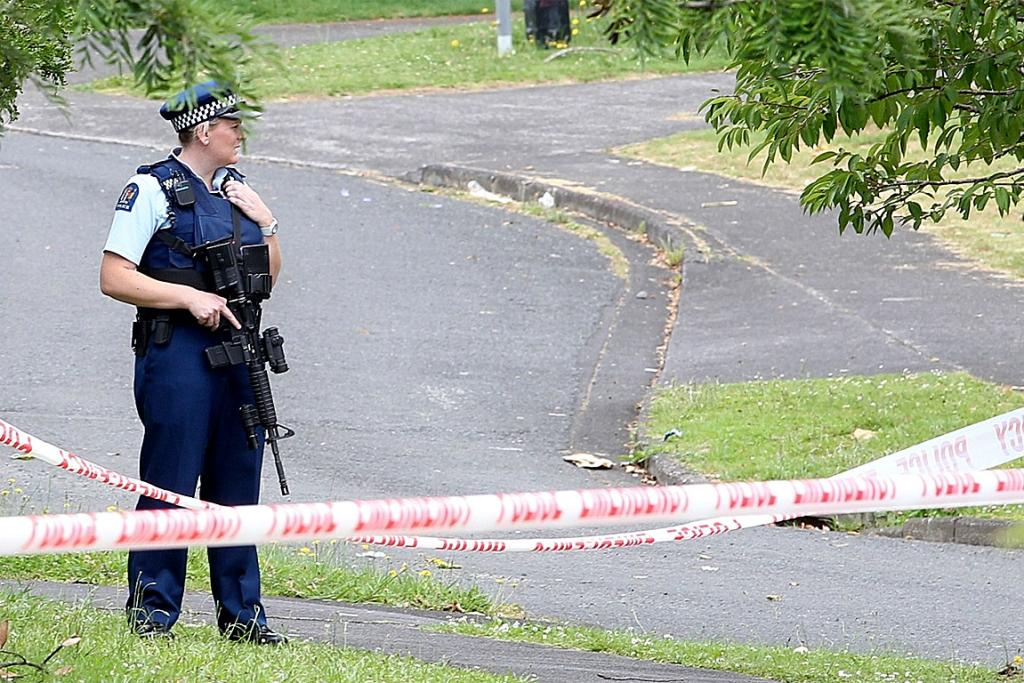 An armed police officer stands guard at the scene of a homicide in Ranui.