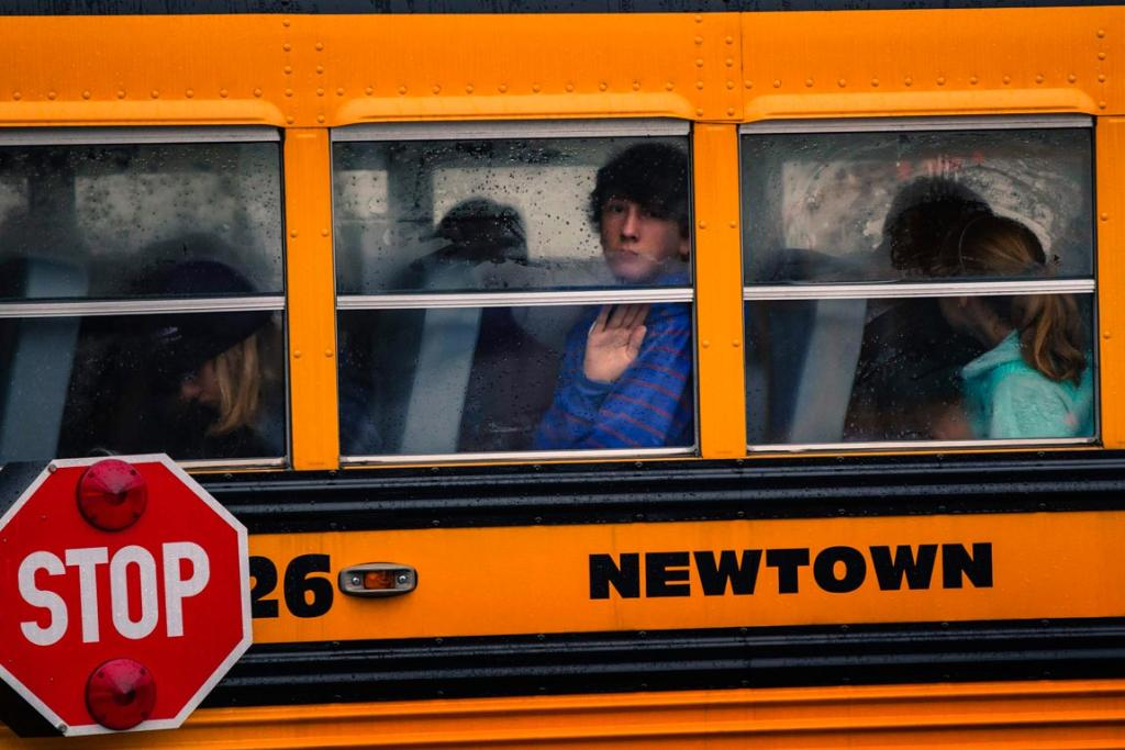 DECEMBER 20: Children look out through condensation in the windows of school bus number 26 as it pulls into Newtown High School in Newtown, Connecticut. Students returned to school in the shattered Connecticut town of Newtown, accompanied by police and counsellors to help them cope with grief and fear after a gunman's shooting rampage killed 26 people at Sandy Hook Elementary School and altered attitudes about gun control in Washington.