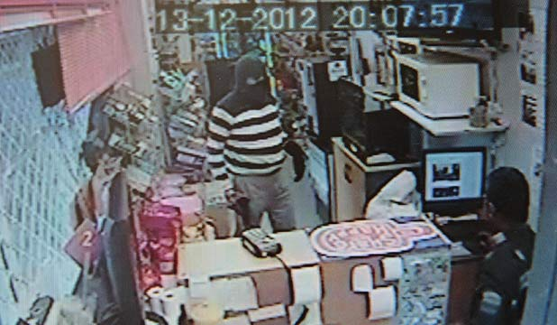 CCTV FOOTAGE: Zahid Chaudry is confronted with the armed robber in his gas station.