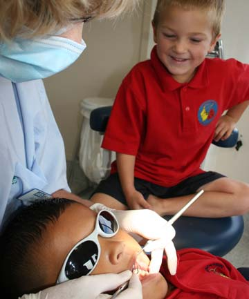 MISSION COMPLETED: Caleb Griffiths-Jones of Henderson South School watches on as his best friend Xanda Tutavake is seen by dental therapist Deborah Hynes in the new transportable dental units.