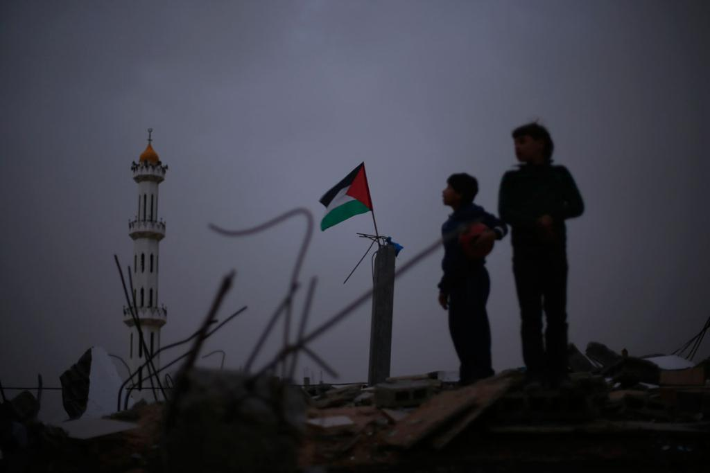 A Palestinian flag flutters as Palestinian boys stand atop the rubble of a house, which witness said was destroyed in an Israeli air strike during an eight-day conflict, in the northern Gaza Strip. Eight days of Israeli air strikes on Gaza and cross-border Palestinian rocket attacks ended in an Egyptian-brokered truce agreement last month calling on Israel to ease restrictions on the territory.