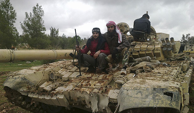 WAGING WAR: Free Syrian Army fighters pose near a tank after the fighters said they defeated government troops in Al-Latameneh, near Hama.