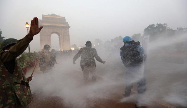 RISING ANGER: Indian security personnel are hit by a water canon as they try to disperse demonstrators during a protest in front of India Gate in New Delhi.