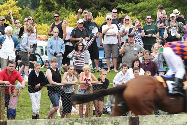 GO YOU GOOD THING: The crowd watches intently as the horses near the finish line.