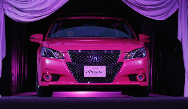 "Toyota's remodeled ""Crown Athlete"" appears between curtains during an unveiling in Tokyo on Christmas Day."