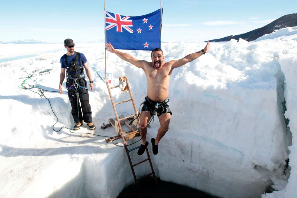 Antarctica New Zealand field training instructor Drew Coleman looks on as New Zealand Army plant operator Joe Kanongata'a does his polar plunge at Scott Base in Antarctica.