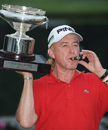 Spain's Miguel Angel Jimenez of Spain with the trophy and his trademark cigar after winning the 2012 Hong Kong Open to be the oldest winner on the European Tour.