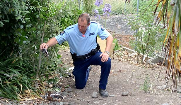 'STUPIDITY': Senior constable Alan Daly empties an alcoholic drink at the crash site.