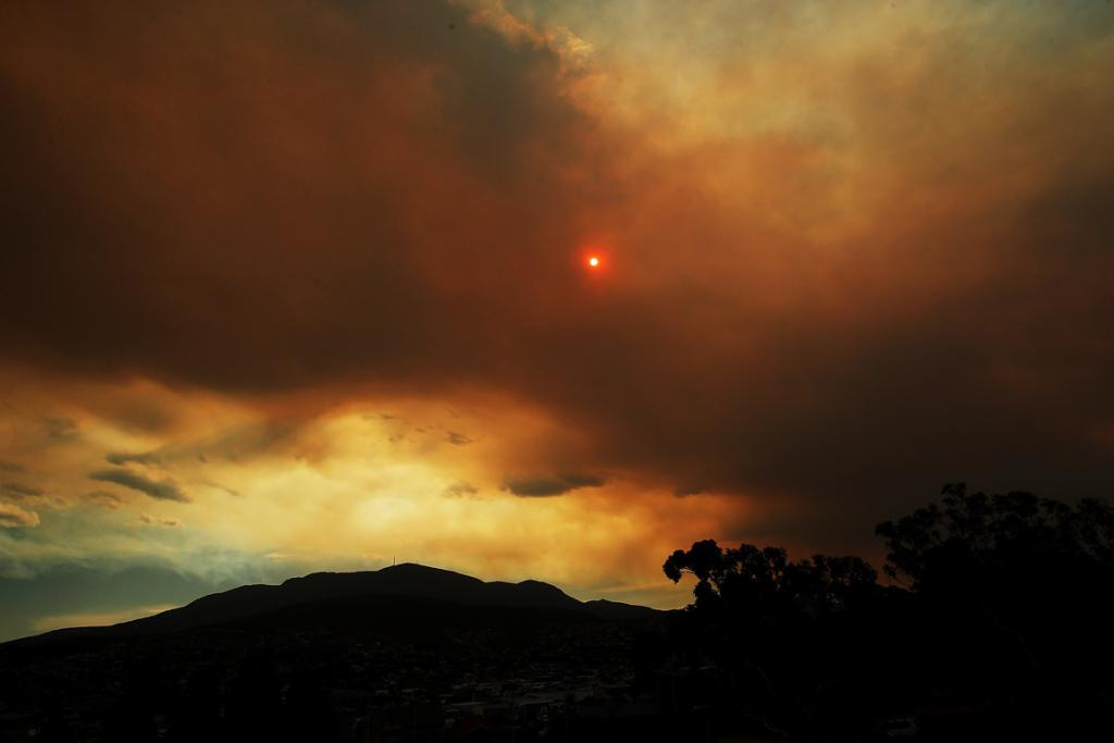 Clouds from a nearby bushfire are seen over Mount Wellington, Tasmania.