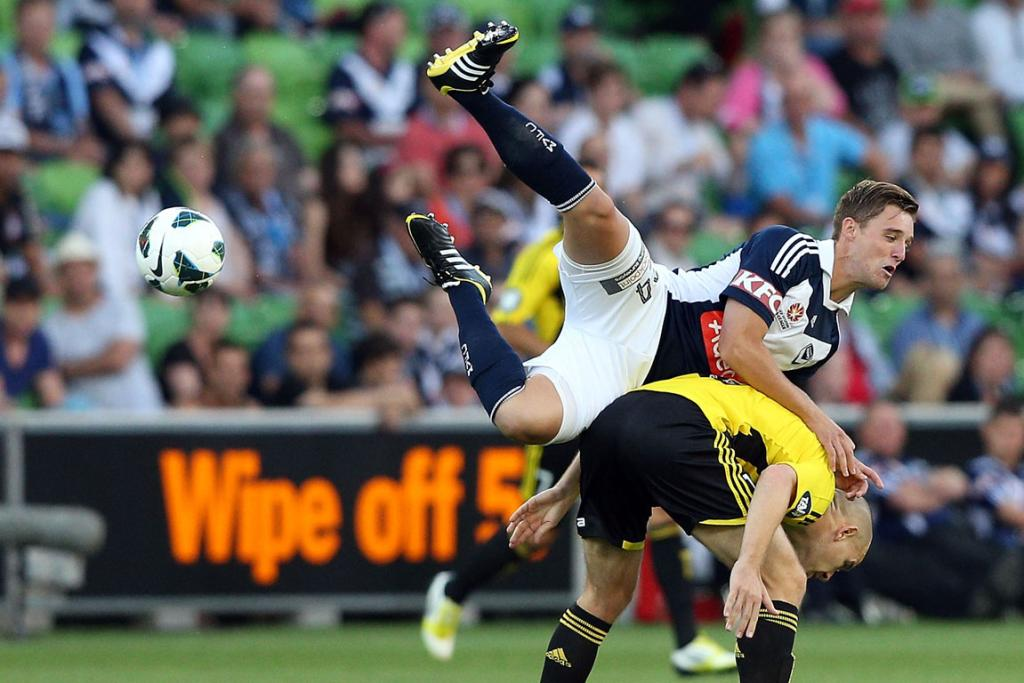 Nick Ansell of the Melbourne Victory jumps on Stein Huysegems of the Wellington Phoenix.