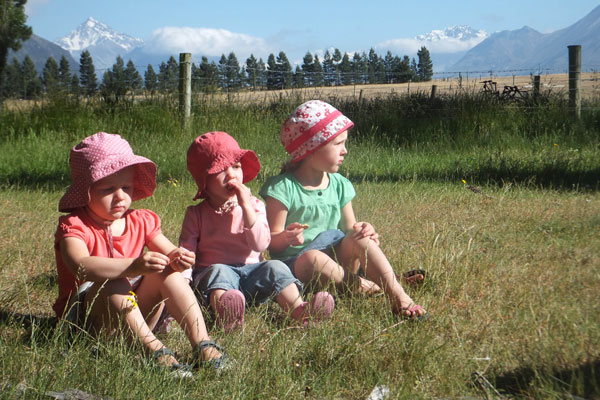 Georgia Martin (3), Lucia Wood (2) and Amelie Martin (4) enjoy a snack in the paddocks of Mesopotamia Station.