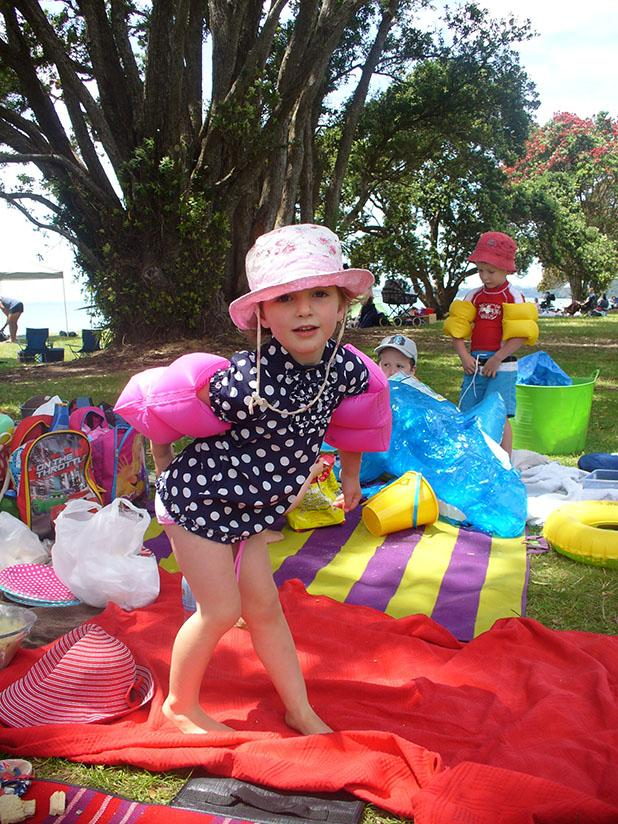 SHOW ME THE WATER: Milly, 3, is set for a swim as she poses underneath a pohutukawa tree.