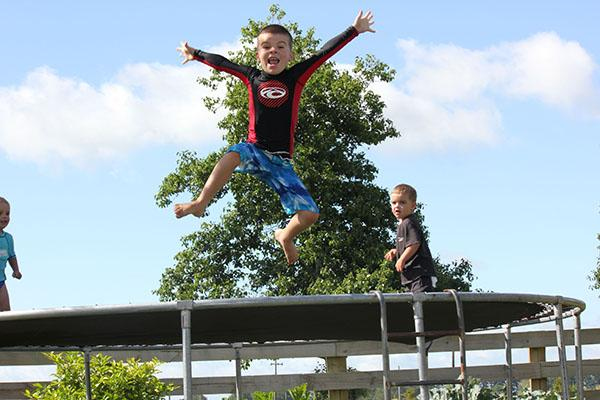 Koby and Cooper Bell watch on as their brother Benji jumps on a trampoline.